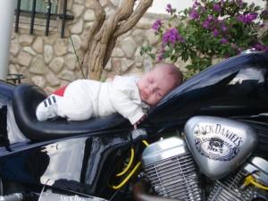 Niño durmiendo sobre moto